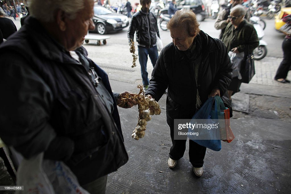 A street trader offers a pensioner bunches of garlic for sale outside the central meat and fish market in Athens, Greece, on Thursday, Nov. 15, 2012. Greece's Supreme Court of Audit ruled that Greek austerity measures including cuts to pensions and an increase in the retirement age may be unconstitutional, state-run Athens News Agency reports, without citing anyone. Photographer: Kostas Tsironis/Bloomberg via Getty Images