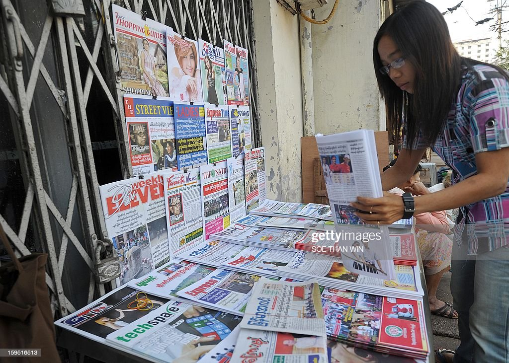 A street vendor arranges newspapers on the road side in downtown Yangon on January 15, 2013. Myanmar is one of the poorest countries in Asia after decades of economic mismanagement and isolation under army rule, but could become Asia's next economic engine if it enacts vast reforms, the IMF said in November of 2012. AFP PHOTO/ Soe Than WIN