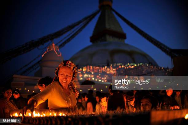 A Street vendor arranging butter lamps which is offered by Nepalese devotee at the premises of Boudhanath Stupa during celebration the 2561 Buddha...