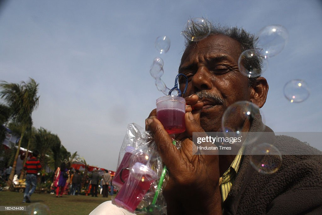 A street vendor blows soap bubbles to attract customers as he sells bottles of bubble solution for Rupees 10 at Sector 21A on February, 23, 2013 in Noida, India.