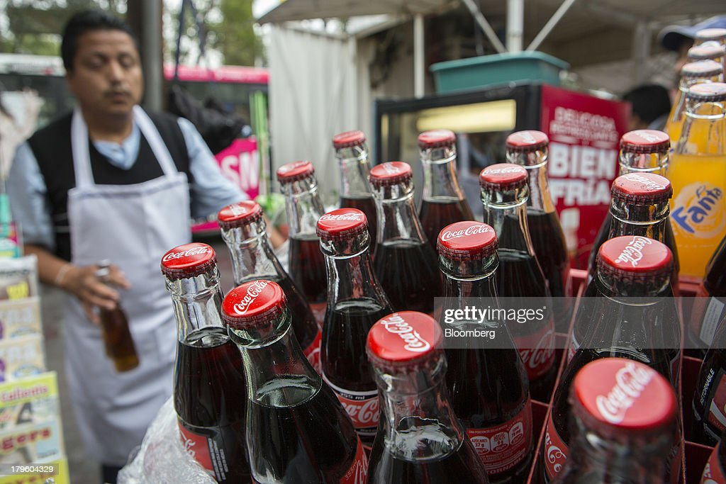 A street vendor carries bottles of soda to customers in Mexico City, Mexico, on Thursday, Sept. 5, 2013. Coca-Cola Femsa SAB, a bottler and distributor of Coca-Cola products in Mexico, agreed to buy Brazils Spaipa SA Industria Brasileira de Bebidas in a cash deal with a total transaction value of $1.86 billion. Photographer: Susana Gonzalez/Bloomberg via Getty Images