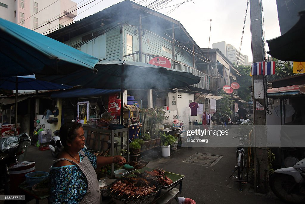 A street vendor cooks food at her stall in a side street off Langsuan road in Bangkok, Thailand, on Tuesday, Dec. 11, 2012. The Crown Property Bureau owns about 41,300 rai (66 square kilometers) of land across the country, about a fifth of which is in Bangkok, according to Aviruth Wongbuddhapitak, an adviser to the CPB who sits on the board of two of its subsidiaries. Photographer: Dario Pignatelli/Bloomberg via Getty Images