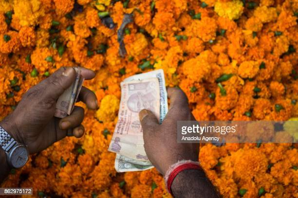 A street vendor counts money while selling marigold flowers on the morning of Diwali festival in Fatehpuri flowers market in Central Delhi India on...