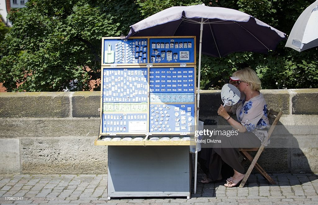 A street vendor fans herself during the hot and sunny day on the Charles Bridge on June 18, 2013 in Prague, Czech Republic. As a heat wave hits the central Europe region, the Karlov district of Prague enjoyed a record breaking temperature of 37 degree Celsius.