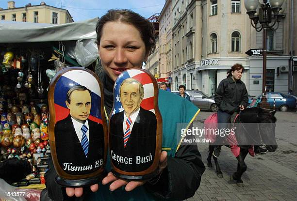 A street vendor holds Russian souvenir matreshka dolls with images of US President George W Bush and Russian President Vladimir Putin May 19 2002 in...