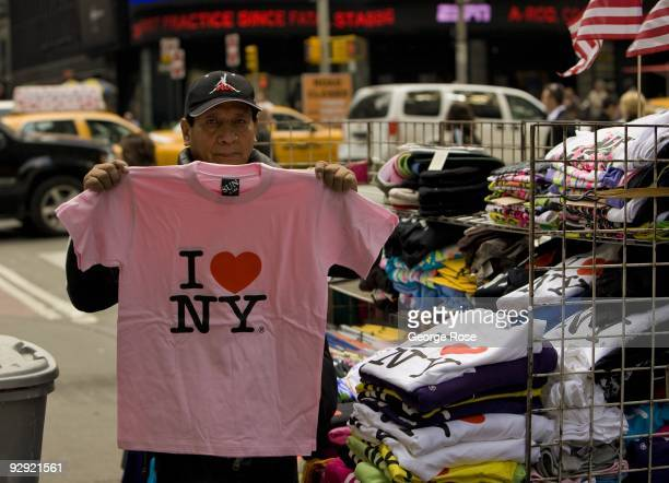 A street vendor holds up an 'I Love New York' tshirt in this 2009 New York NY early evening cityscape photo
