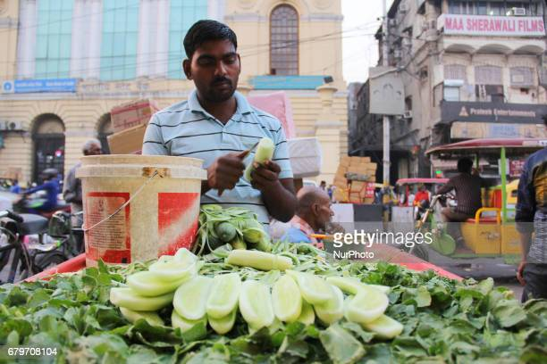 A street vendor is selling peeledoff cucumbers with a pinch of salt in Old Delhi India on May 6 2017