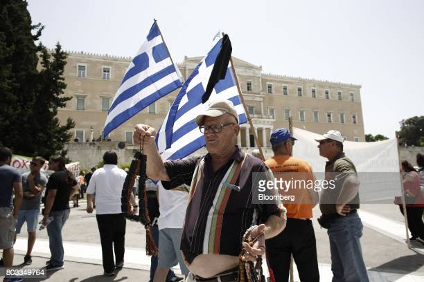 A street vendor looks for customers during a demonstration outside the Greek parliament by municipal contract workers in Athens Greece on Thursday...