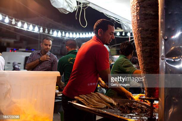 A street vendor makes shwarma sandwiches March 18 2013 in Baghdad Iraq Ten years after the regime of Saddam Hussein was toppled from power Baghdad...