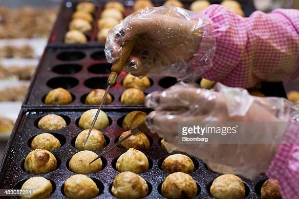 A street vendor makes takoyaki octopus dumplings at a food stall in the Bupyeong Kkangtong night market in Busan South Korea on Tuesday July 28 2015...