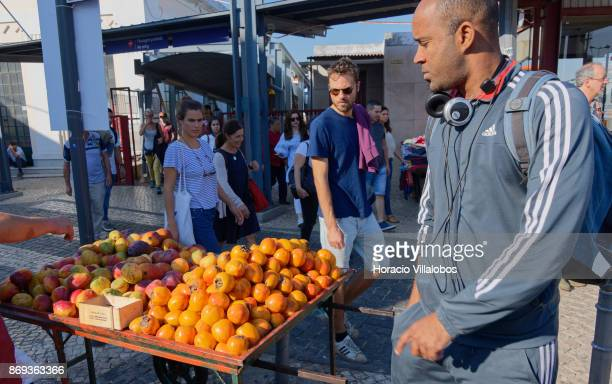A street vendor offers mangoes and persimmons to arriving travelers outside the ferry terminal on October 31 2017 in Cacilhas Portugal Cais do Sodre...