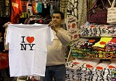 A street vendor on 7th Avenue near Broadway and Times Square holds up a 'I Love New York' tshirt in this 2009 New York NY early afternoon cityscape...