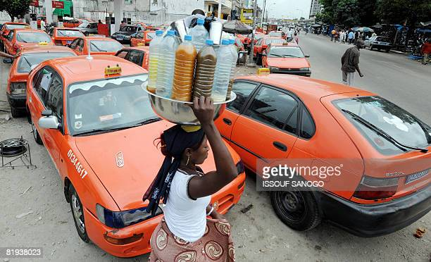 A street vendor passes by taxi parked on the second day of a strike conducted by taxi and minibus drivers in protest against soaring fuel prices on...