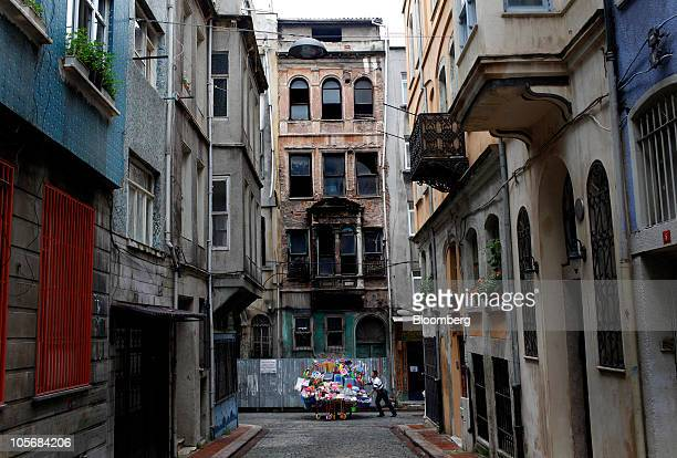 A street vendor passes old houses in the Fener Balat neighborhood of Istanbul Turkey on Monday Oct 18 2010 Turkish developers are flocking to...