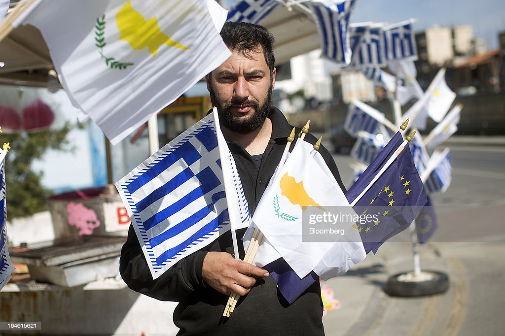 A street vendor poses for a photograph with Greek, Cypriot and European Union (EU) flags for sale to mark Greek national day in Nicosia, Cyprus, on Monday, March 25, 2013. In a replay of tensions over aid for Greece at the outset of the crisis, European governments had wrangled over aid for Cyprus for nine months, exposing holes in the revamped economic management system that was built in three years of emergency policymaking, often at all-night summits. Photographer: Photographer: Simon Dawson/Bloomberg via Getty Images