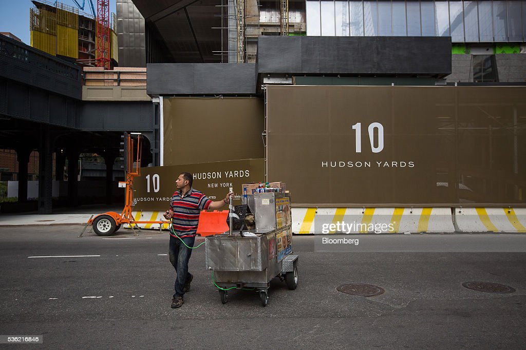A street vendor pulls a hot dog cart past 10 Hudson Yards, center, home to Coach Inc.'s new offices, in New York, U.S., on Tuesday, May 31, 2016. The first skyscraper at Related Cos.'s $25 billion Hudson Yards project opened Tuesday after three and a half years of construction, bringing office workers to a once-desolate area of Manhattan's far west side that's now transforming into a new business enclave. Photographer: Michael Nagle/Bloomberg via Getty Images