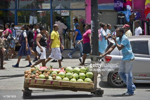 A street vendor pushes a cart full of fruits at a busy shopping street in downtown Kingston June 28 2012 Jamaica will celebrate its 50th anniversary...