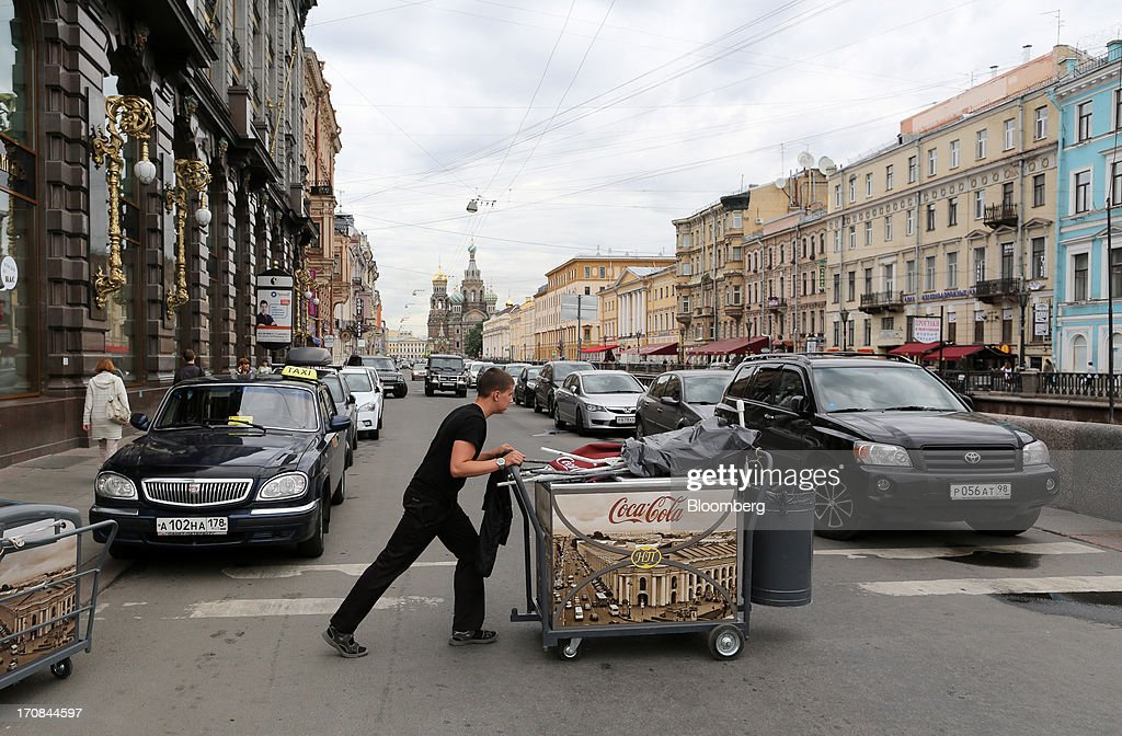 A street vendor pushes a drinks cart advertising Coca Cola Co. across a street ahead of the St. Petersburg International Economic Forum 2013 (SPIEF) in St. Petersburg, Russia, on Wednesday, June 19, 2013. The Russian Deputy Prime Minister Igor Shuvalov told the conference that the country's World Trade Organization accession negotiations could be further delayed unless several remaining disputed matters are solved. Photographer: Andrey Rudakov/Bloomberg via Getty Images