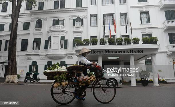 A street vendor pushes her bicycle past the iconic hotel Metropole in Hanoi on January 19 2017 / AFP / HOANG DINH NAM