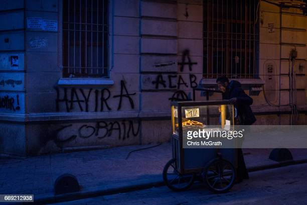 A street vendor pushes his cart past 'Hayir' graffiti on April 16 2017 in Istanbul Turkey According to unofficial results 5121% were in favour and...