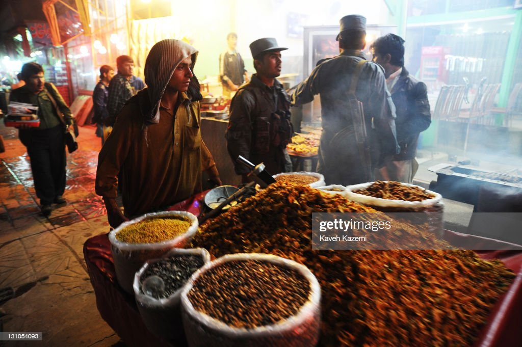 A street vendor pushes his cart past policemen talking on the street in the early hours of evening on October 16, 2011 in Kabul, Afghanistan.