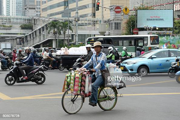 A street vendor selling coffee and other beverages cycles through an intersection in Jakarta Indonesia on Friday Jan 15 2016 A deadly gunandsuicide...
