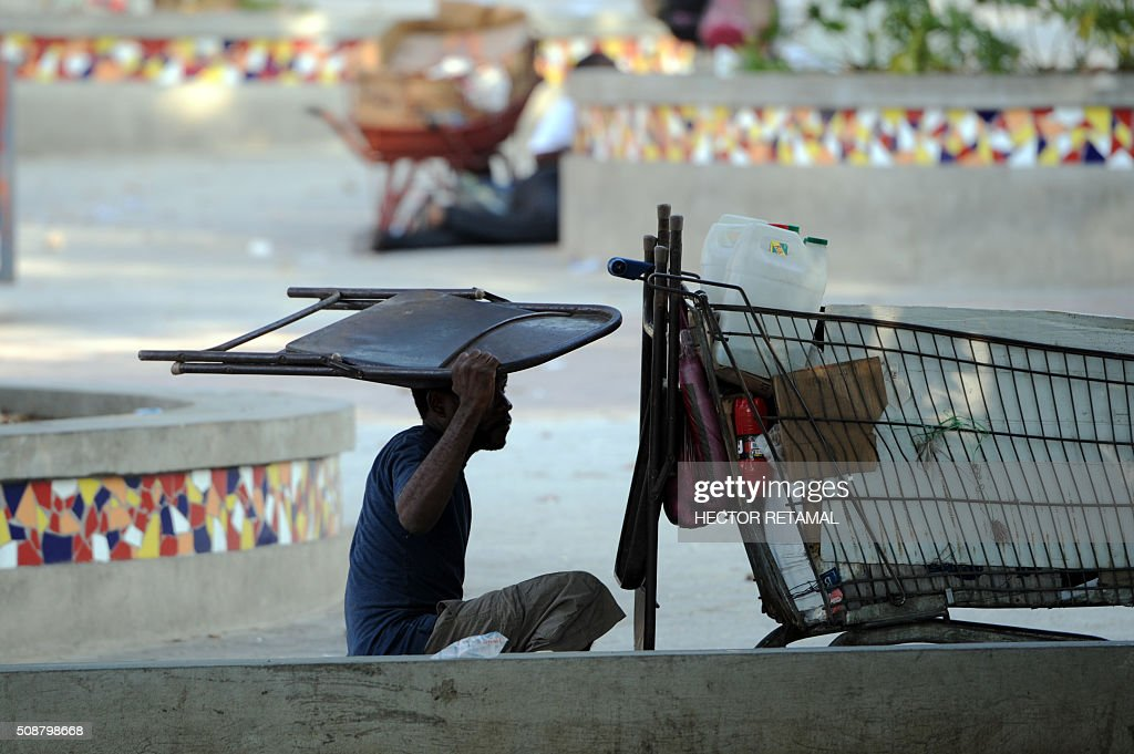 A street vendor selling sodas shields himself with a chair during a protest by opposition demonstrators against Haitian President Michel Martelly, in Port-au-Prince, on February 6, 2016. Haitian politicians inked a last-minute agreement to install a transitional government, just hours before President Michel Martelly was scheduled to step down with no replacement in line. / AFP / HECTOR RETAMAL