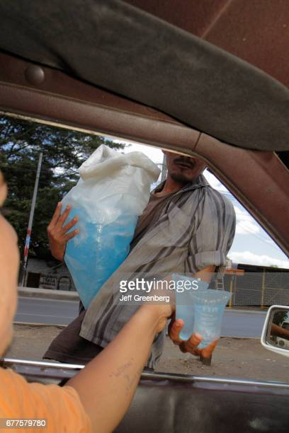 A street vendor selling water to a taxi cab driver at Carretera Norte