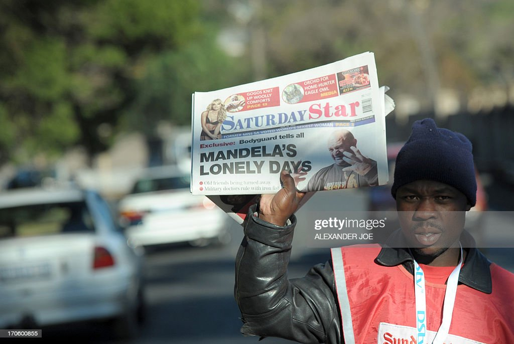 A street vendor sells a local newspaper in Johannesburg on June 15, 2013. One of Nelson Mandela's bodyguards on June 15 accused his medical team of isolating the ailing icon as he continued to receive hospital treatment for a lung infection. According to Shaun van Heerden, a member of the elite presidential protection police service, the team led by the army Surgeon-General Vejay Ramlakan has long imposed strict visitor controls for Mandela. 'At times it felt like he was back in prison,' Van Heerden said.