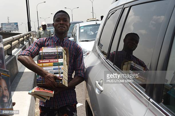 A street vendor sells books between cars on a road of Lagos on July 12 2016 Lagos State Government has begun the enforcement of the law banning...