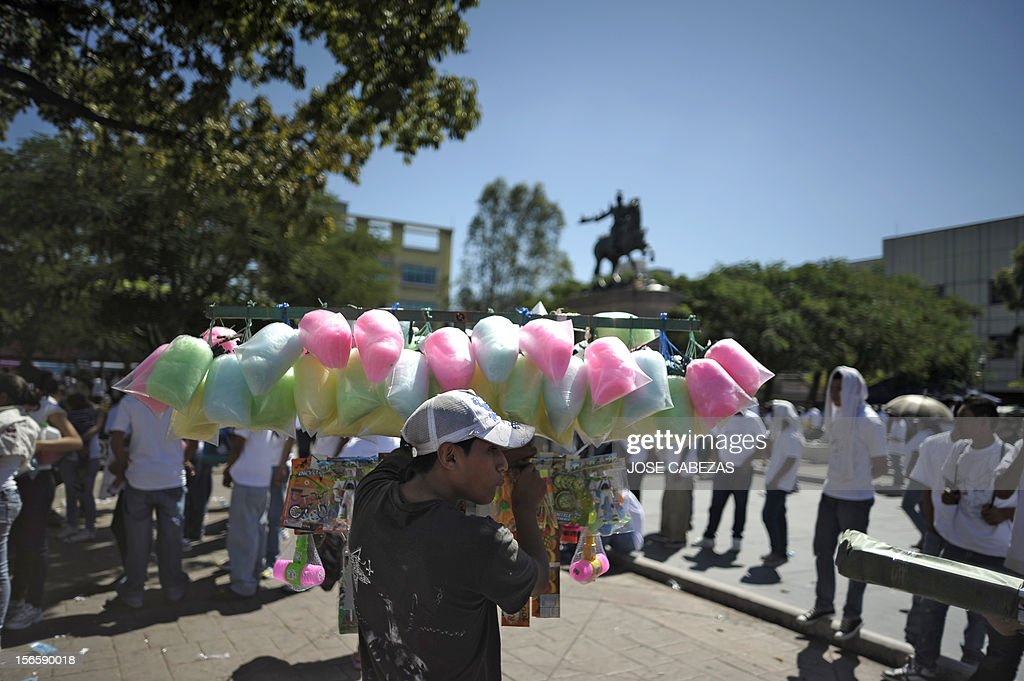 A street vendor sells cotton candy during a religious service with gang members at Gerardo Barrios square in downtown San Salvador on November 17, 2012. Leaders of the Anglican, Lutheran and other churches showed Saturday their support to a truce process among gangs, which allowed the reduction of daily murders from an average of 14 to 5,5. AFP PHOTO/ Jose CABEZAS