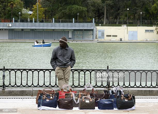A street vendor sells counterfeit designer handbags at the Retiro Park in Madrid on November 13 2014 AFP PHOTO / GERARD JULIEN