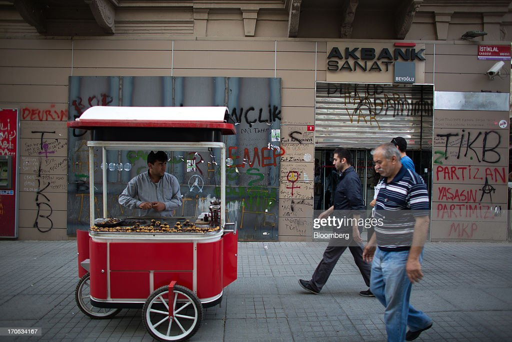 A street vendor sells food from a stall outside a closed Akbank TAS bank branch covered in anti-government graffiti near Taksim Square in Istanbul, Turkey, on Thursday, June 13, 2013. The law forbids the sale of alcohol at night and near schools and mosques, going against the secular traditions of the Muslim-majority country of 74 million, where many people drink and women often choose not to cover their hair. Photographer: Lam Yik Fei/Bloomberg via Getty Images