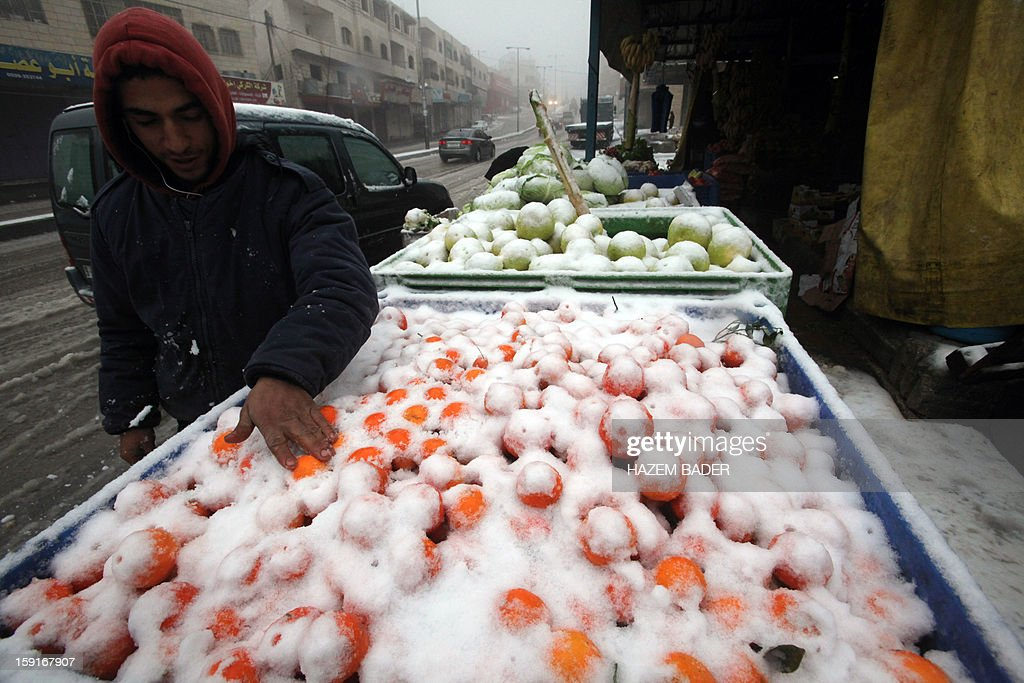 A street vendor sells fruit and vegetables covered in snow on the side of the road in the West Bank town of Hebron on January 9, 2013. Extreme weather, including torrential rains and heavy winds, killed four people in Israel and the Palestinian territories on January 8, as widespread flooding swept the Middle East.
