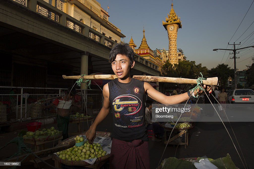 A street vendor sells fruit in Yangon, Myanmar, on Tuesday, Jan. 22, 2013. Myanmar cleared about $1 billion in overdue debt with the Asian Development Bank and World Bank using a bridge loan from Japan, opening the door for increased lending as the country seeks to overhaul its infrastructure. Photographer: Brent Lewin/Bloomberg via Getty Images