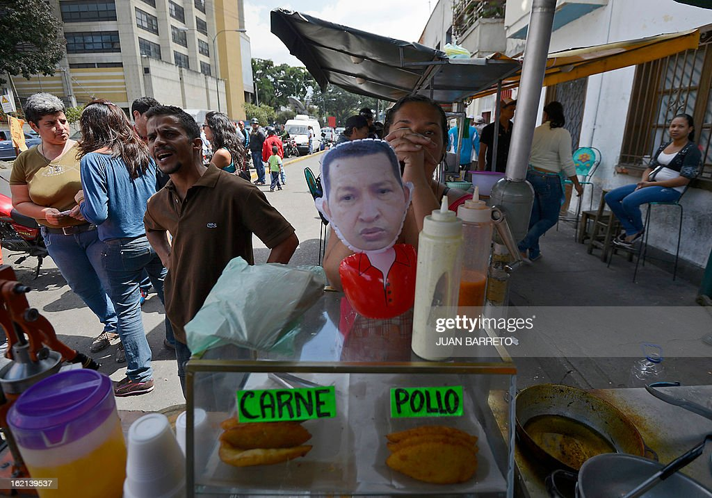 A street vendor sells pies in front of of the military hospital in Caracas where Venezuelan President Hugo Chavez was hospitalized following his return from Cuba on the eve, on February 19, 2013. Chavez returned to Venezuela early on Monday after spending more than two months in Cuba for cancer surgery and treatment, announcing his surprise homecoming via Twitter. 'We have arrived again to the Venezuelan motherland,' Chavez wrote. AFP PHOTO/Juan Barreto