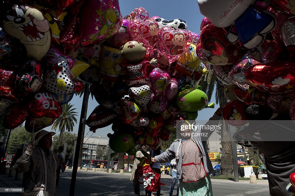 A street vendor sells Valentine's Day gifts during Mexico's 'One Billion Rising' flashmob against violence against women, at the Republic Square in front of the Monument to the Mexican Revolution, in Mexico City on February 14, 2013. The 'One Billion Rising' is a protest held in about two hundred countries around the world on St Valentine's day. AFP PHOTO/Yuri CORTEZ