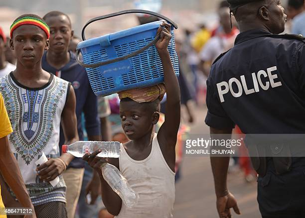 A street vendor sells water bottles while security officials check people queuing to get into the New Kintele stadium in Brazzaville before the...