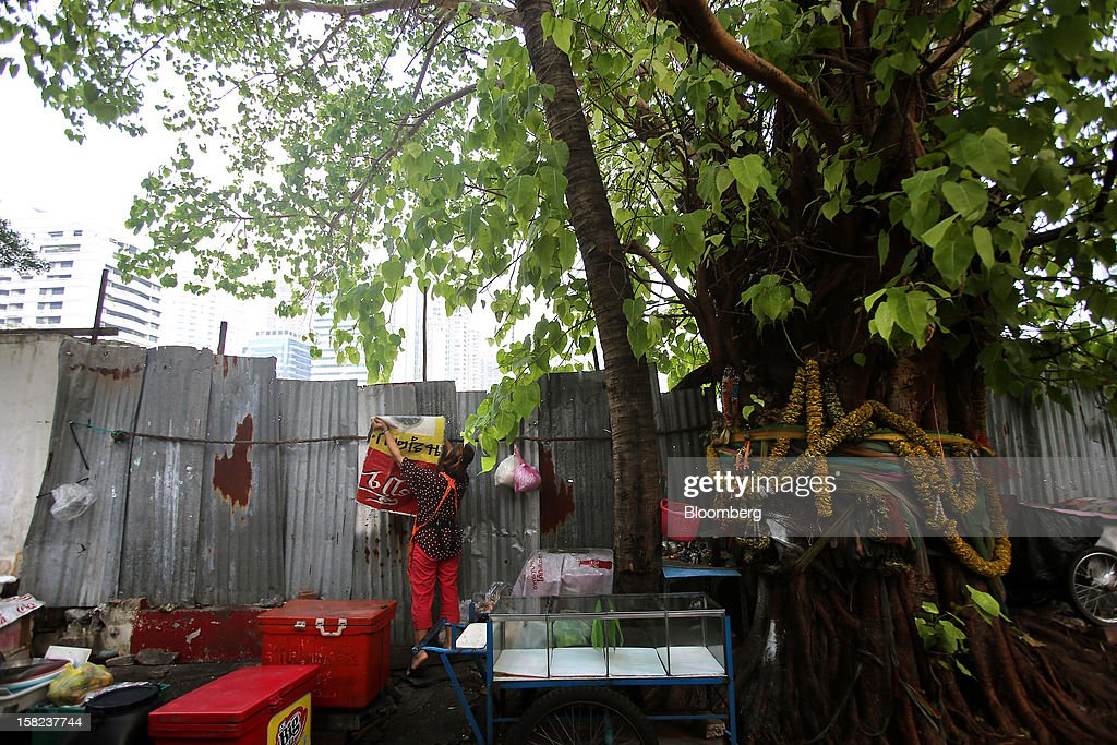 A street vendor sets up her stall next to fencing demarcating a plot of land in a side street off Langsuan road in Bangkok, Thailand, on Tuesday, Dec. 11, 2012. The Crown Property Bureau owns about 41,300 rai (66 square kilometers) of land across the country, about a fifth of which is in Bangkok, according to Aviruth Wongbuddhapitak, an adviser to the CPB who sits on the board of two of its subsidiaries. Photographer: Dario Pignatelli/Bloomberg via Getty Images