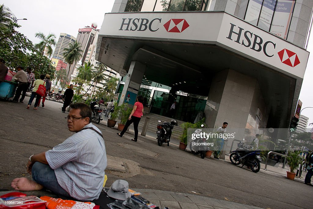 A street vendor sits outside an HSBC Holdings Plc bank branch in Kuala Lumpur, Malaysia, on Wednesday, Jan. 16, 2013. While many developed countries have faltered, Malaysia's gross domestic product growth has exceeded 5 percent for five quarters with domestic demand countering a slowdown in exports. Photographer: Lam Yik Fei/Bloomberg via Getty Images