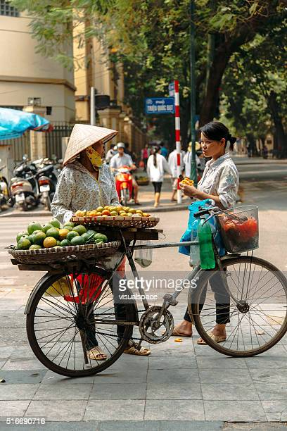 Street vendor talking with customer in Ho Chi Minh City