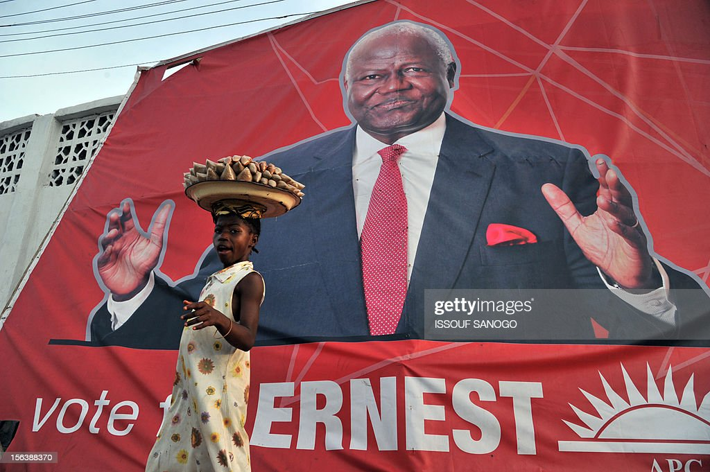A street vendor walks past a poster bearing a picture of Sierra Leone's President Ernest Bai Koroma on November 14, 2012 in Freetown, ahead of general elections in Sierra Leone on November 17, 2012. The west African nation, which despite significant advances remains one of the world's poorest and most under-developed a decade after the end of its civil conflict, will also vote for a new parliament.