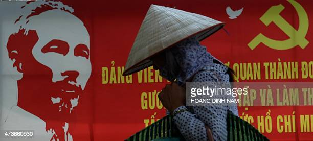 A street vendor walks past a poster marking the 125th birthday anniversary of late president Ho Chi Minh founder of today's communist Vietnam on a...