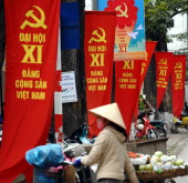A street vendor walks past a raw of red banners marking the upcoming national congress of the ruling Vietnam communist party hung up on trees along a...