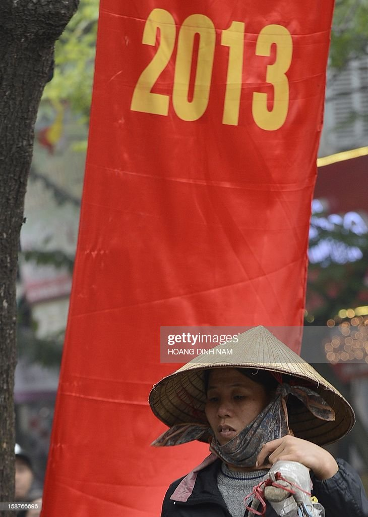 A street vendor walks past a red banner marking the 2013 new year in downtown Hanoi on December 28, 2012. Vietnam's economic growth slowed to the weakest pace in 13 years in 2012, according to published official statistics, piling more pressure on the country's rulers. Gross domestic product grew by 5.03 percent this year while inflation slowed to 6.8 percent in December year-on year from 7.08 percent in November. AFP PHOTO/HOANG DINH Nam