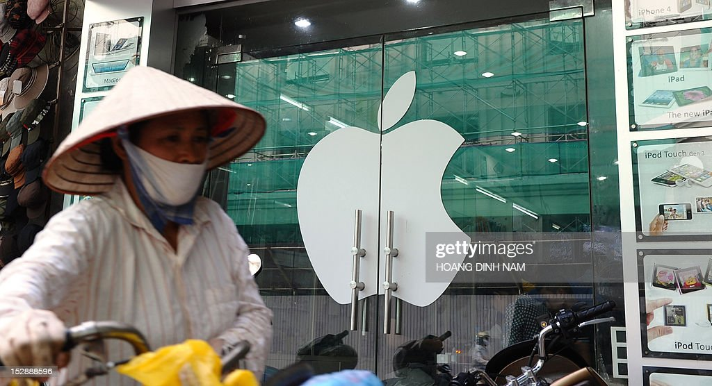A street vendor walks past a shop selling Apple products with a digital advertising display announcing that Apple's smart phone Iphone 5 is available for sale on a street in downtown Hanoi on September 28, 2012. Not being among themarkets choosen for Apple's inaugural sale of the Iphone 5, Vietnam's smart phone market gets feverish with hi-tech lovers and wealthy people ready to pay up to 23 million dongs or 1,100 USD for an Iphone 5 16G model, all of which are imported by individuals from Singapore, Hong Kong or the US. AFP PHOTO/HOANG DINH Nam