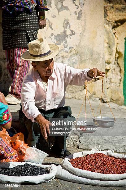 Street vendor weighing beans