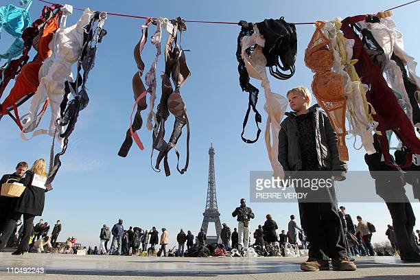Street vendors are at work with tourists on the Parvis des droits de l'homme in Paris on March 20 as demonstrators hung up bras during a 'Spring...