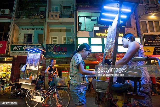 Street vendors cook and sell dried seafood from their bicycle carts in District 1 in Ho Chi Minh City Vietnam on March 154 2015