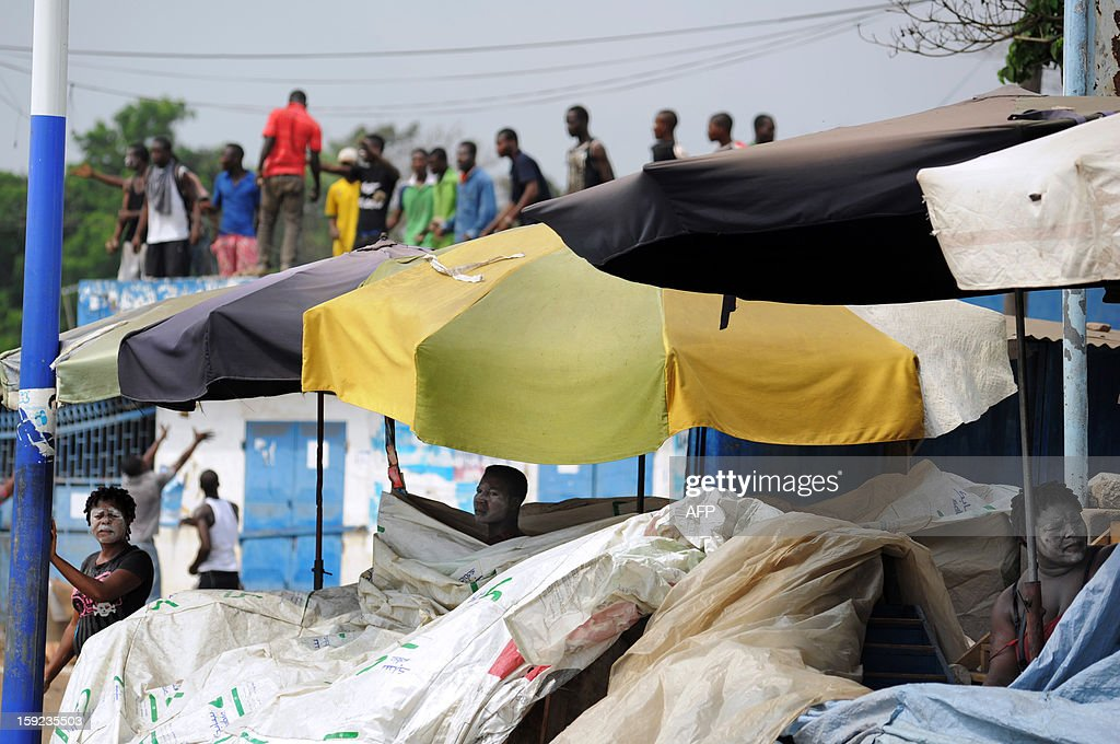 Street vendors hide in their stalls as protesters stand on rooftops during clashes with security forces on January 10, 2013 on the first of a three-day planned demonstration in Lome, Togo. Togolese security forces on January 10 fired tear gas at tyre-burning youths after preventing an opposition march considered illegal in the latest such confrontation ahead of upcoming elections. Opposition groups are calling for the resignation of President Faure Gnassingbe, whose family has been in power for over 40 years.
